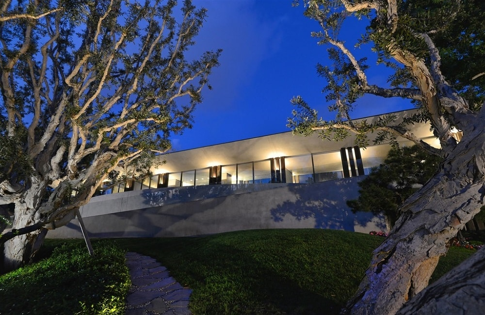 This is a view of the front of the house that showcases the warm glow of the house at night. This also shows the trees of the landscaping. Image courtesy of Toptenrealestatedeals.com.