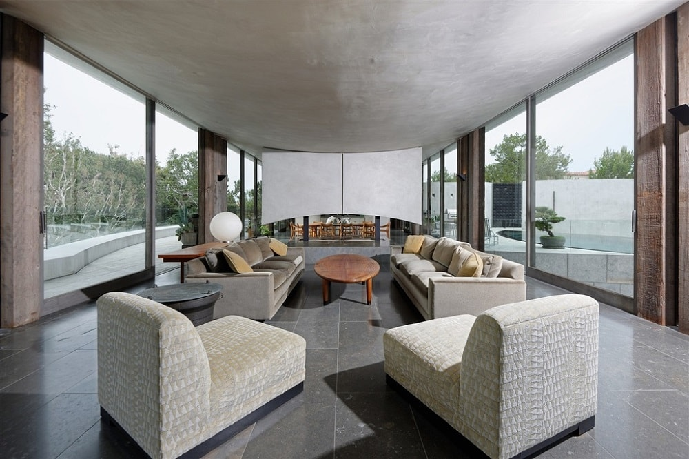 This is the living room that has gray tones to its ceiling, flooring tiles and sofa set. These are then complemented by the large glass walls on two sides. Image courtesy of Toptenrealestatedeals.com.