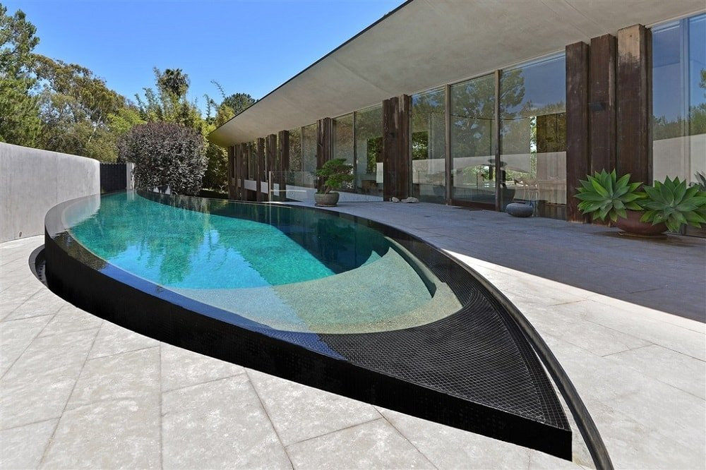This is the swimming pool of the house that is shaped like a tip of a painter's brush. This view also shows the glass walls of the house. Image courtesy of Toptenrealestatedeals.com.