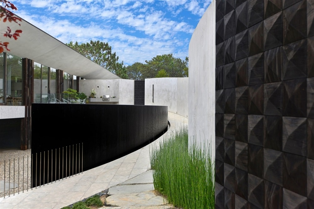 This is a side look at the pool of the house. Here you can see the black bottom of the pool closely that contrasts the surrounding concrete and shrubs lining the wall. Image courtesy of Toptenrealestatedeals.com.