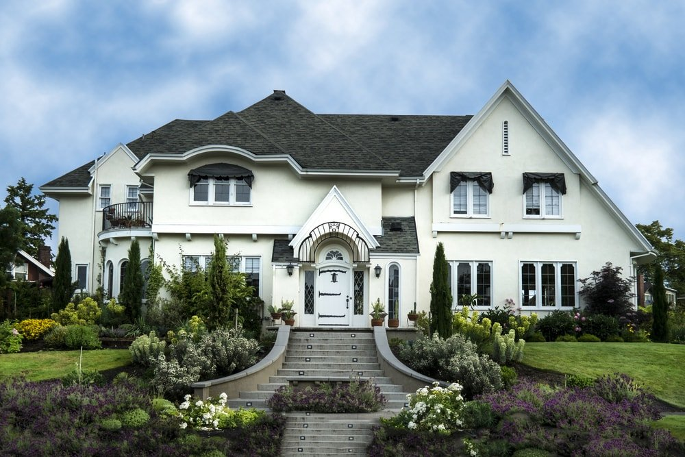 A large white stucco luxury house with a landscaped front yard and steps leading to the front entrance.