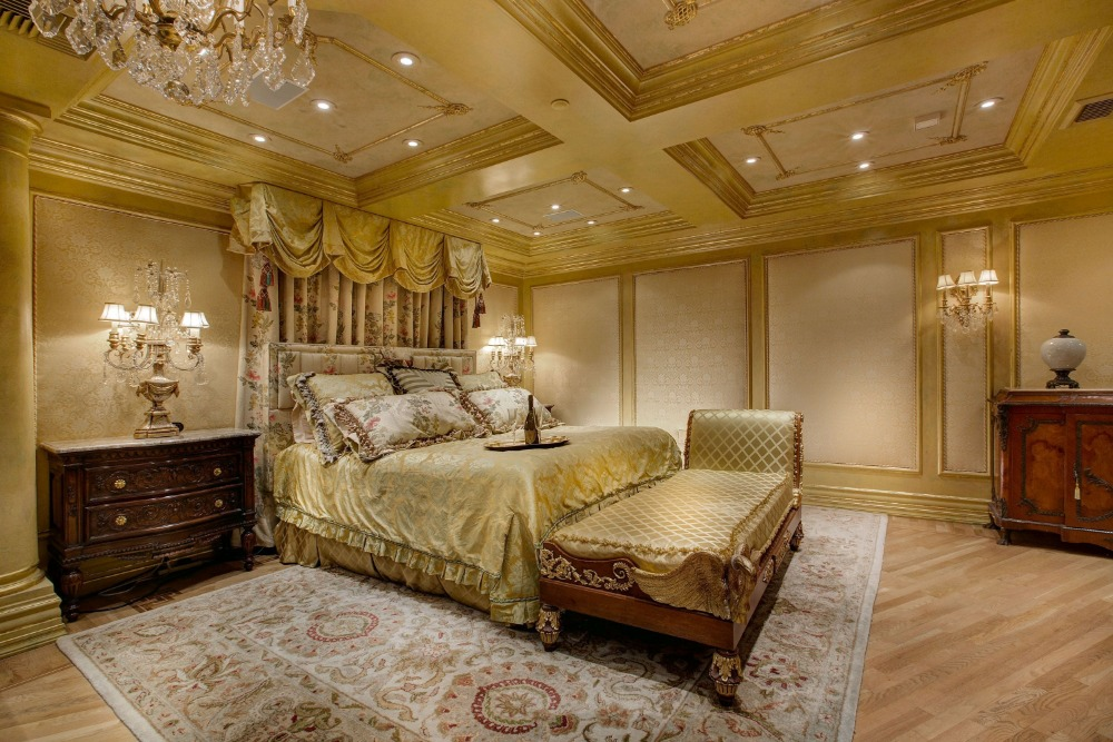 Large primary bedroom with elegant walls and ceiling along with a luxurious bed set. Images courtesy of Toptenrealestatedeals.com.
