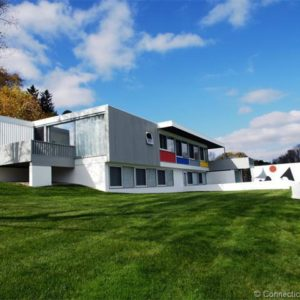 This is a front look at the house with a modernist look of straight lines and blocks accented by the glass walls and a few splashes of colors. Image courtesy of Toptenrealestatedeals.com.