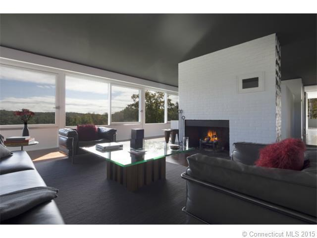 The living room has a glass-top coffee table across from the fireplace surrounded by black cushioned armchairs and a long sofa on a dark floor that matches the ceiling. Image courtesy of Toptenrealestatedeals.com.