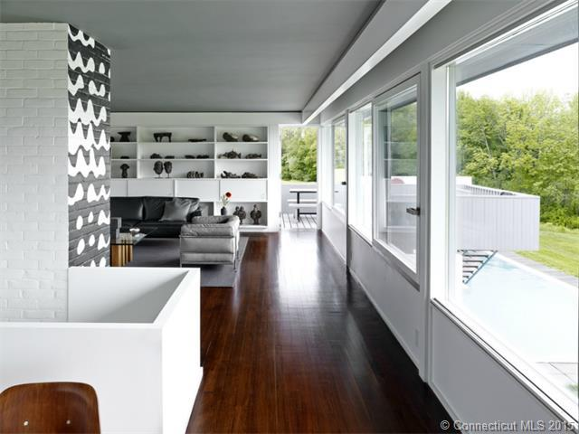 This is a look at the living room from the hallway beside the fireplace wall. Here you can see the wide glass walls on one side that brings in an abundance of natural lighting. Image courtesy of Toptenrealestatedeals.com.