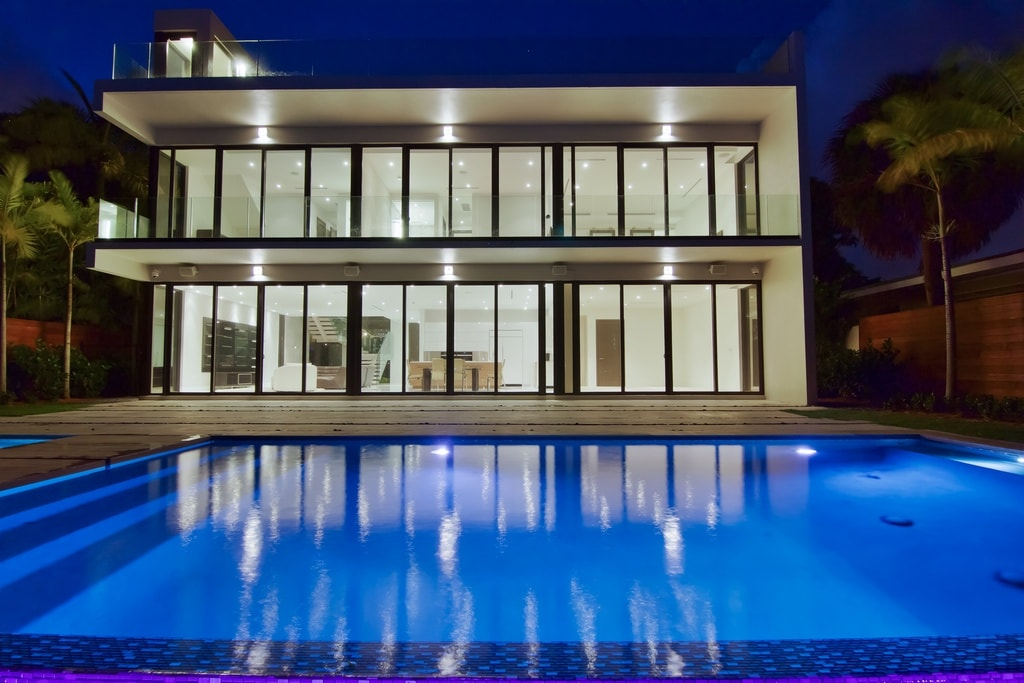 This is the view of the house from the backyard pool. Here you can appreciate the large glass walls of the Contemporary-style house along with the glass railing of the rooftop level. This also highlights the glow of the house and the pool. Image courtesy of Toptenrealestatedeals.com.