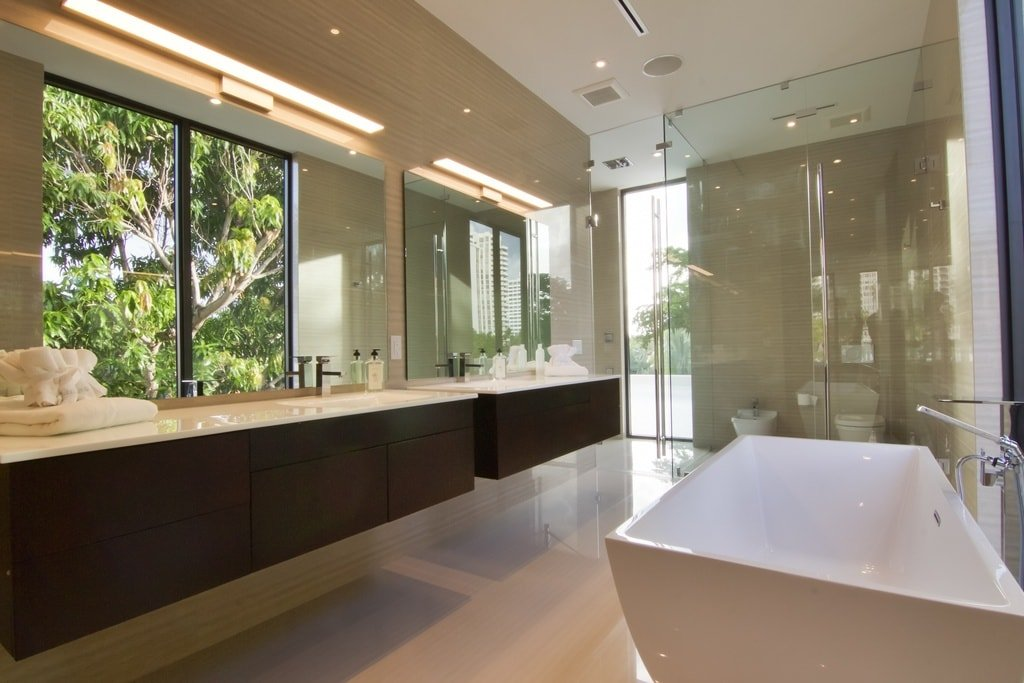 The primary bathroom has a bathtub across from the two-sink floating vanity that has a dark brown tone that contrasts the beige floor and walls. Image courtesy of Toptenrealestatedeals.com.