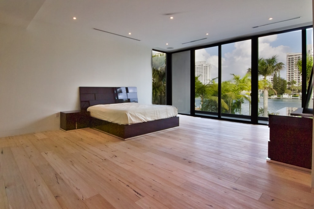 The spacious primary bedroom has light hardwood flooring that makes the dark brown tone of the bed stand out. These are paired with white walls, a white ceiling and glass walls. Image courtesy of Toptenrealestatedeals.com.