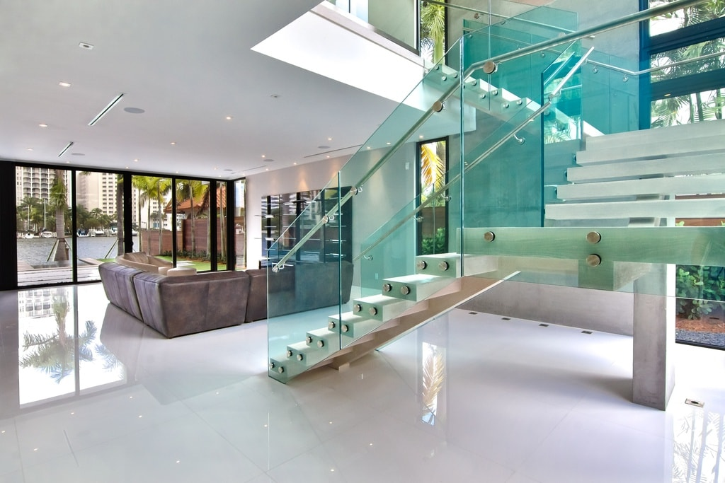 Upon entry of the house, you are welcomed by this foyer that has a modern staircase in the middle that has glass railings on its side for a unique look. Image courtesy of Toptenrealestatedeals.com.
