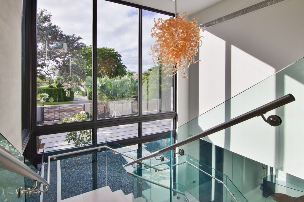 This is a view of the foyer from the second-floor landing. You can see here that it has a tall ceiling paired with a tall glass wall and a large decorative chandelier. Image courtesy of Toptenrealestatedeals.com.