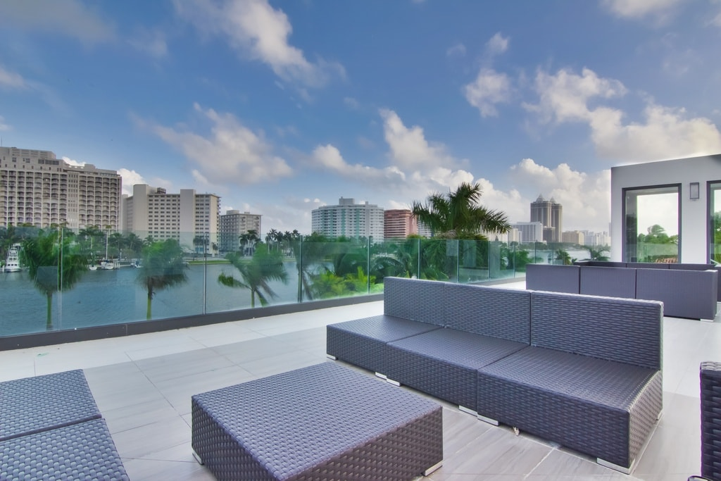 The spacious rooftop is fitted with gray woven wicker furniture that provides a nice spot for relaxing with the view of the tropical trees and water scenery. Image courtesy of Toptenrealestatedeals.com.