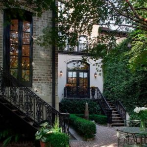 This is a look at the back of the house. Here you can see that it has a secret garden closed off by tall walls filled with creeping plants and tall trees. The small area is fitted with an outdoor dining set that is surrounded by shrubs, trees and the exteriors of the house. Image courtesy of Toptenrealestatedeals.com.