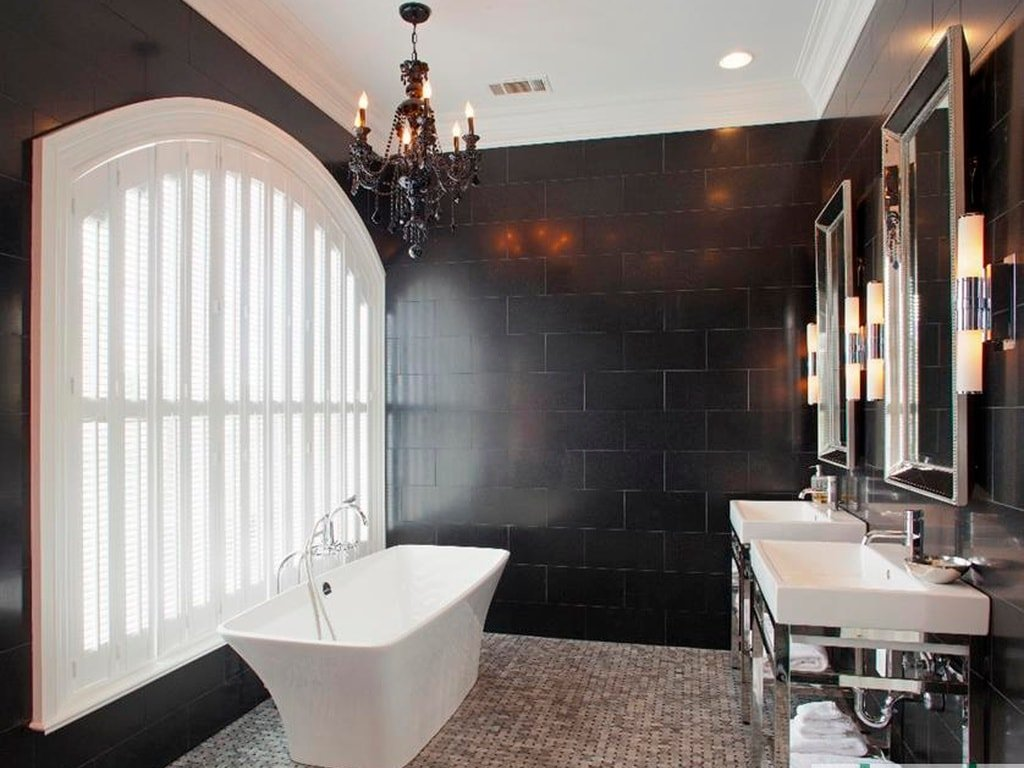 This bathroom has black walls that contrast the white frame of the large arched window by the white freestanding bathtub. Image courtesy of Toptenrealestatedeals.com.