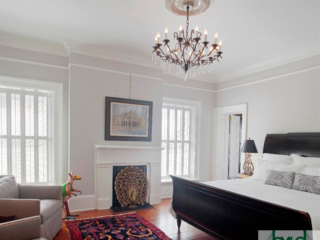 This bedroom's light tones and white molding that blends with the mantle of the fireplace are all contrasted by the black sleigh bed paired with a black table lamp on the side table. Image courtesy of Toptenrealestatedeals.com.
