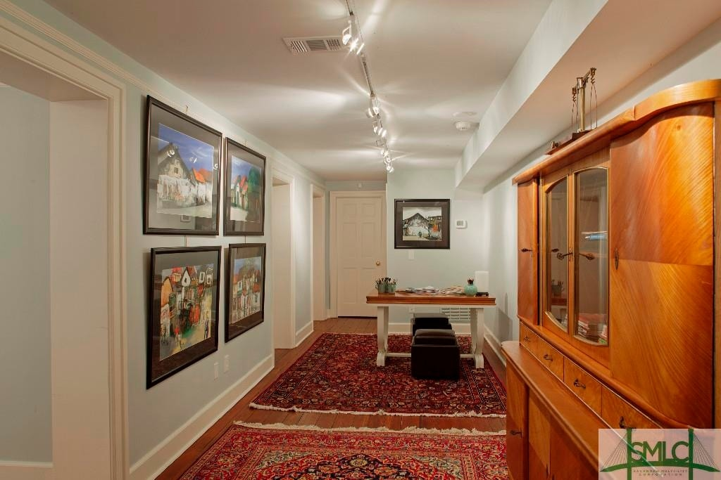 This spacious hallway is fitted with a table and a couple small cushioned stools for a crafts corner adorned with wall-mounted artworks. Image courtesy of Toptenrealestatedeals.com.
