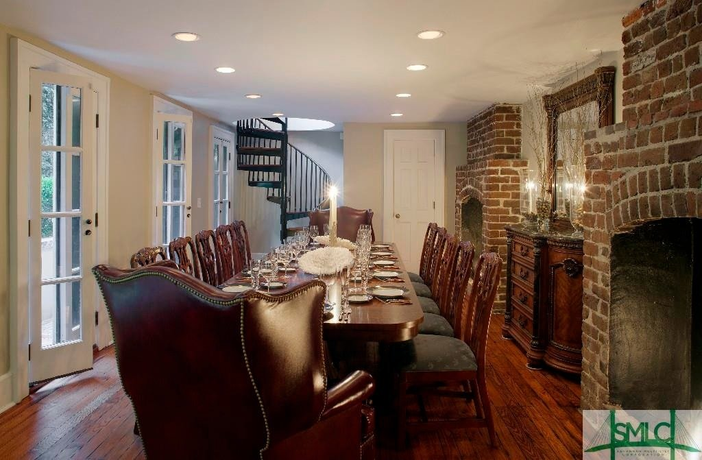 This formal dining room is dominated by a large rectangular wooden dining table that matches the chairs and the hardwood flooring. On the side, you will see a red brick fireplace beside a dining room cabinet. Image courtesy of Toptenrealestatedeals.com.