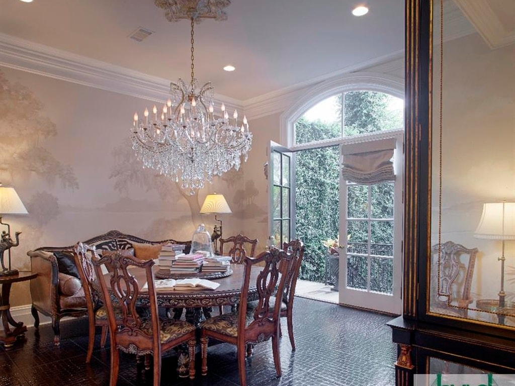This is a more intimate dining area with a round wooden dining table topped with a large chandelier. This is illuminated by the large glass balcony doors with an arched transom window. Image courtesy of Toptenrealestatedeals.com.