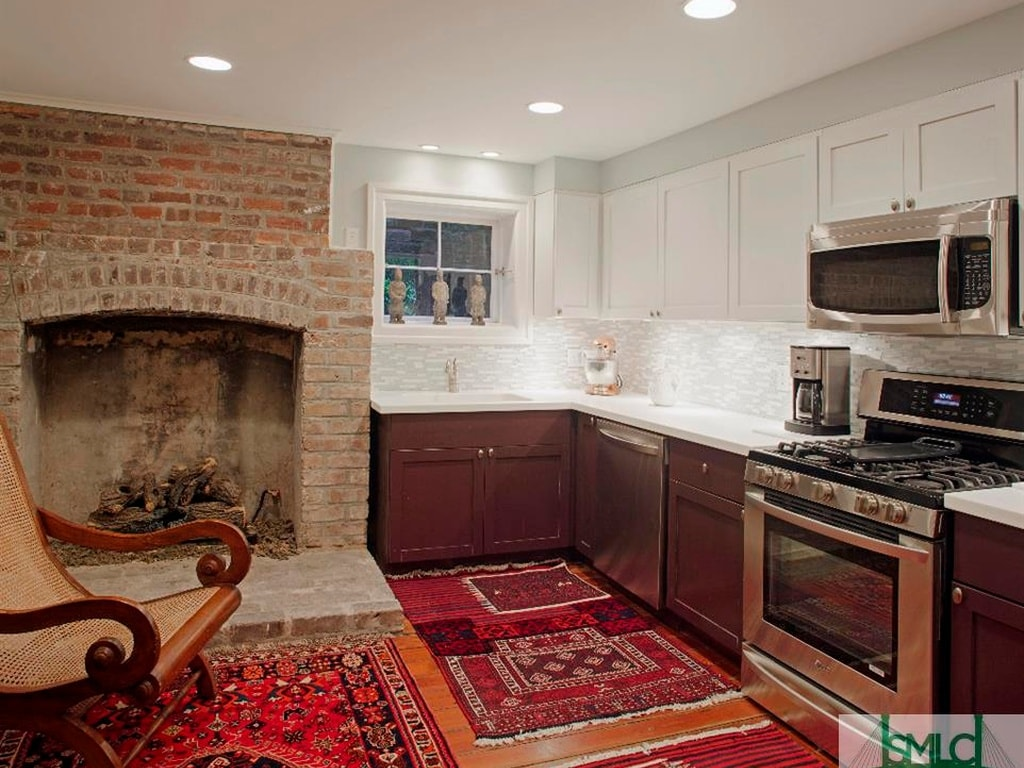 The kitchen has a large red brick fireplace, dark brown cabinetry and red patterned area rugs on the hardwood flooring. Image courtesy of Toptenrealestatedeals.com.
