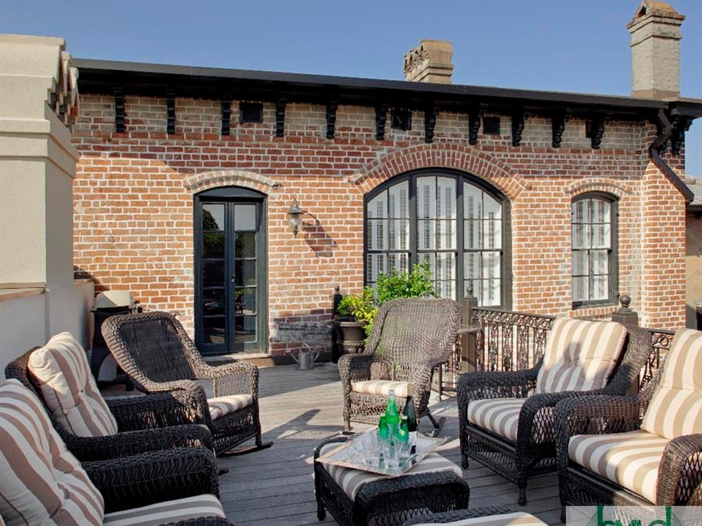 This is the rooftop terrace of the mansion that is fitted with outdoor armchairs and coffee tables. You can also see here the red brick walls and arched windows of the house. Image courtesy of Toptenrealestatedeals.com.
