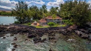 This is an aerial shot of the beach house that faces the ocean on a rocky edge. You can see here that the house has terracotta-toned roofs that makes it stand out against the background of tall tropical trees. Image courtesy of Toptenrealestatedeals.com.
