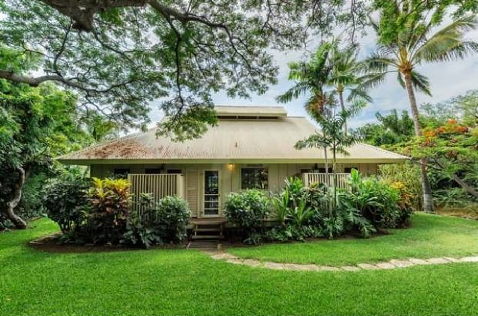 This is the guest house with a beige exterior that is complemented by the surrounding shrubs and tall trees. Image courtesy of Toptenrealestatedeals.com.