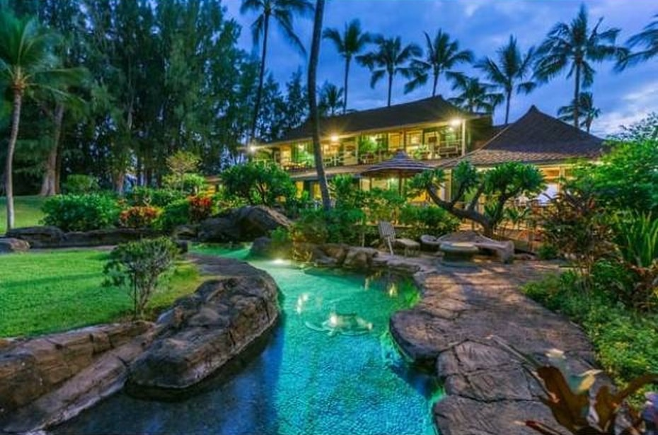 This is a view of the house from the vantage of the pool that is designed to have natural-looking edges with stone formations and landscaping filled with grass and tropical plants. Image courtesy of Toptenrealestatedeals.com.