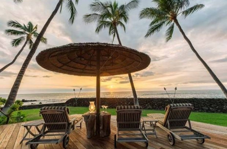 This is the part of the patio facing the ocean. It is fitted with lawn chairs and a large umbrella on the wooden deck floor adorned with tall tropical trees. Image courtesy of Toptenrealestatedeals.com.