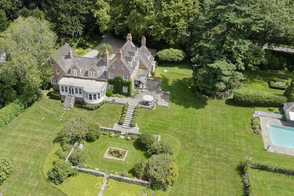 This is an aerial view of the house showing the large grass lawns surrounding the house along with tall trees. Image courtesy of Toptenrealestatedeals.com.