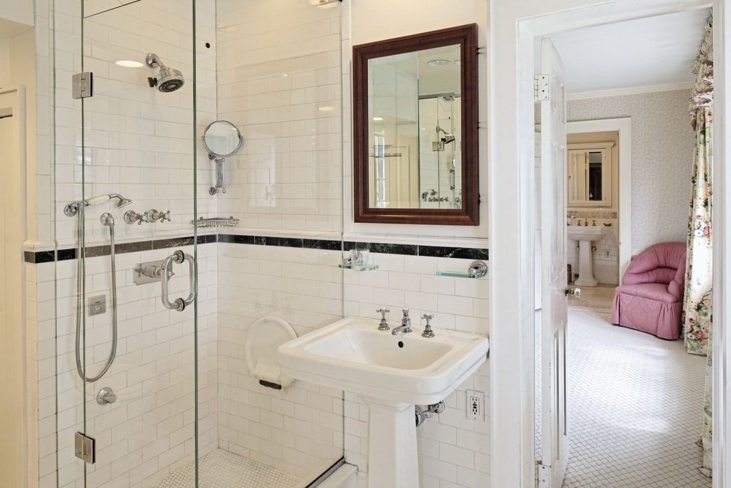 This is a close look at one of the bathrooms that has a white pedestal sink beside the glass-enclosed shower area. Image courtesy of Toptenrealestatedeals.com.