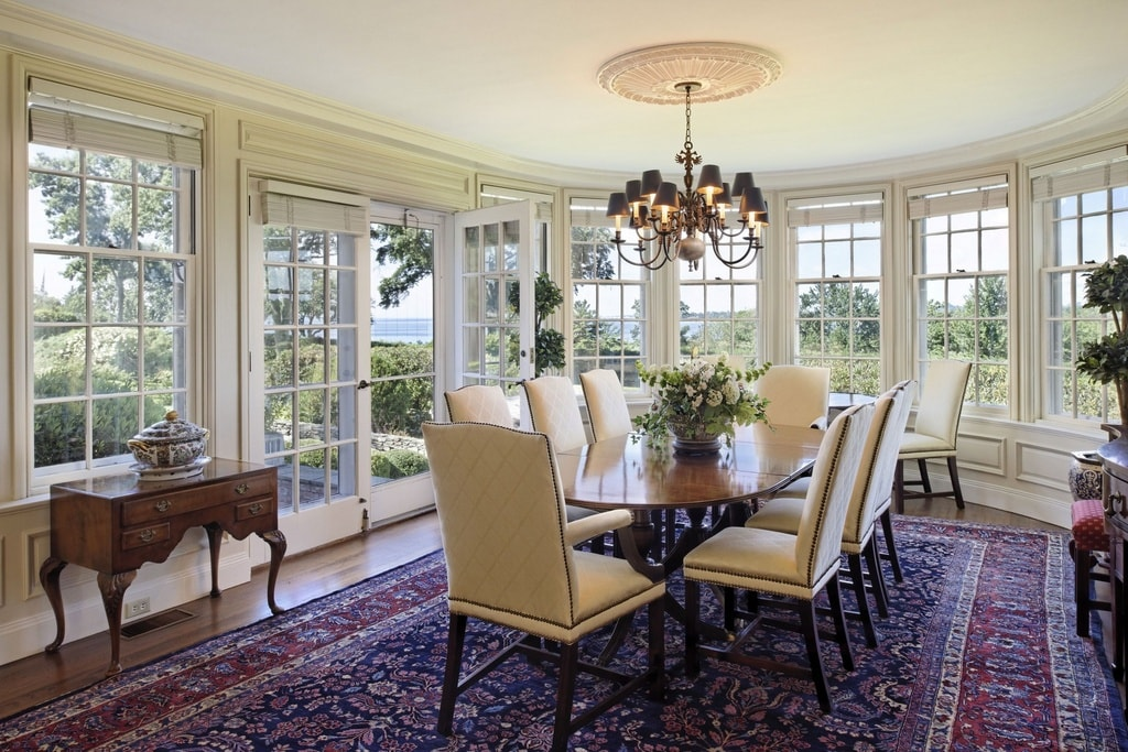 The formal dining room has a purple patterned area rug that gives contrast to the beige chairs surrounding the wooden dining table topped with a chandelier. Image courtesy of Toptenrealestatedeals.com.