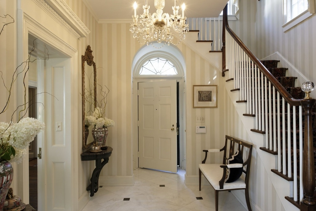Upon entry of the house, you are welcomed by this foyer with striped beige wallpaper, a built-in console table, a chandelier and a wooden bench on the side of the staircase. Image courtesy of Toptenrealestatedeals.com.