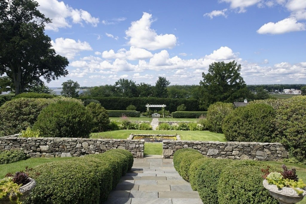 This is a close look at the garden that has a landscaping filled with mosaic stone low walls, shrubs and grass lawns to a background of tall trees. Image courtesy of Toptenrealestatedeals.com.