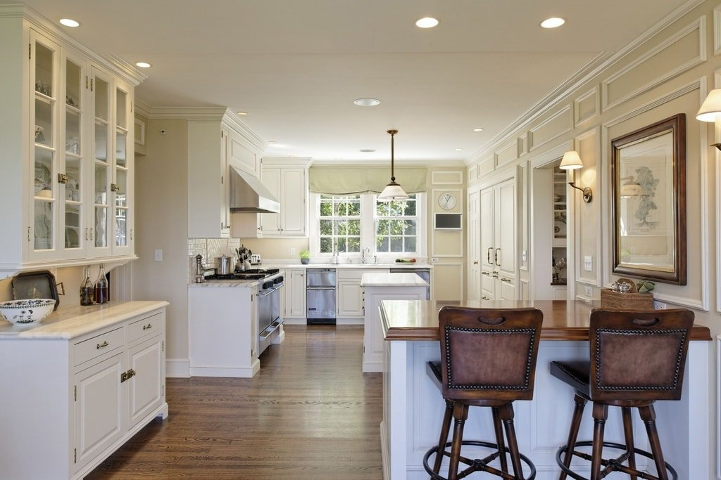 The spacious kitchen has an island, a peninsula and cabinetry lining the walls that match the beige ceiling. These are then complemented by the hardwood flooring. Image courtesy of Toptenrealestatedeals.com.