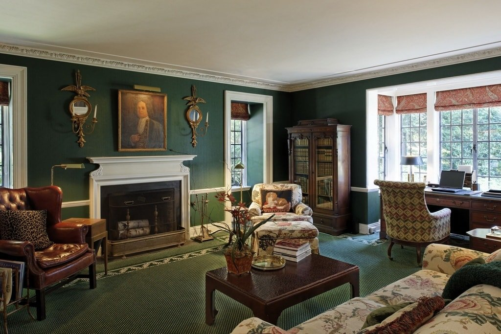 This is the home office with green walls to match the green carpeted flooring. These also make the fireplace stand out with its white mantle topped with a classic painting. Image courtesy of Toptenrealestatedeals.com.