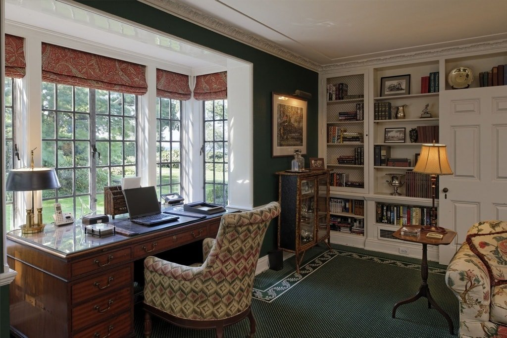 This is a closer look at the wooden desk of the home office against the window alcove. On the side, you can see a set of built-in bookshelves. Image courtesy of Toptenrealestatedeals.com.