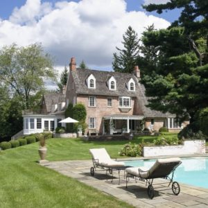 This is a view of the house from the vantage of the backyard swimming pool. Here you can see the large home with its earthy exterior walls, tall chimneys and dormer windows that bring character to the house along with the landscaping. Image courtesy of Toptenrealestatedeals.com.