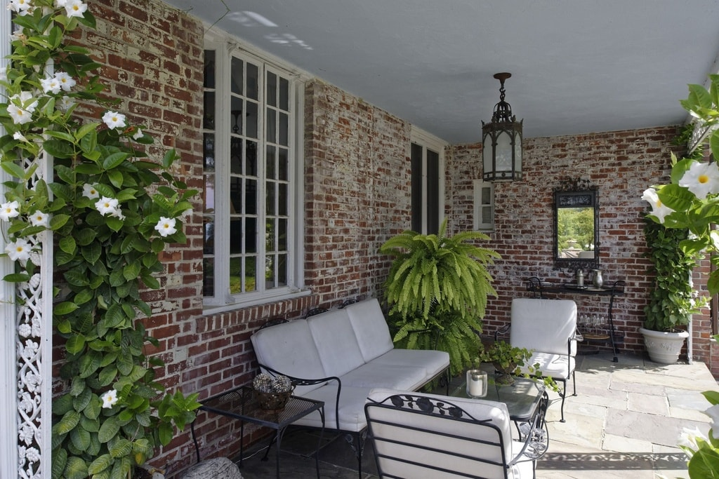 This is a patio with white cushions on its wrought-iron sofa set that makes then stand out against the red brick exterior wall of the house. These are then adorned with potted plants. Image courtesy of Toptenrealestatedeals.com.