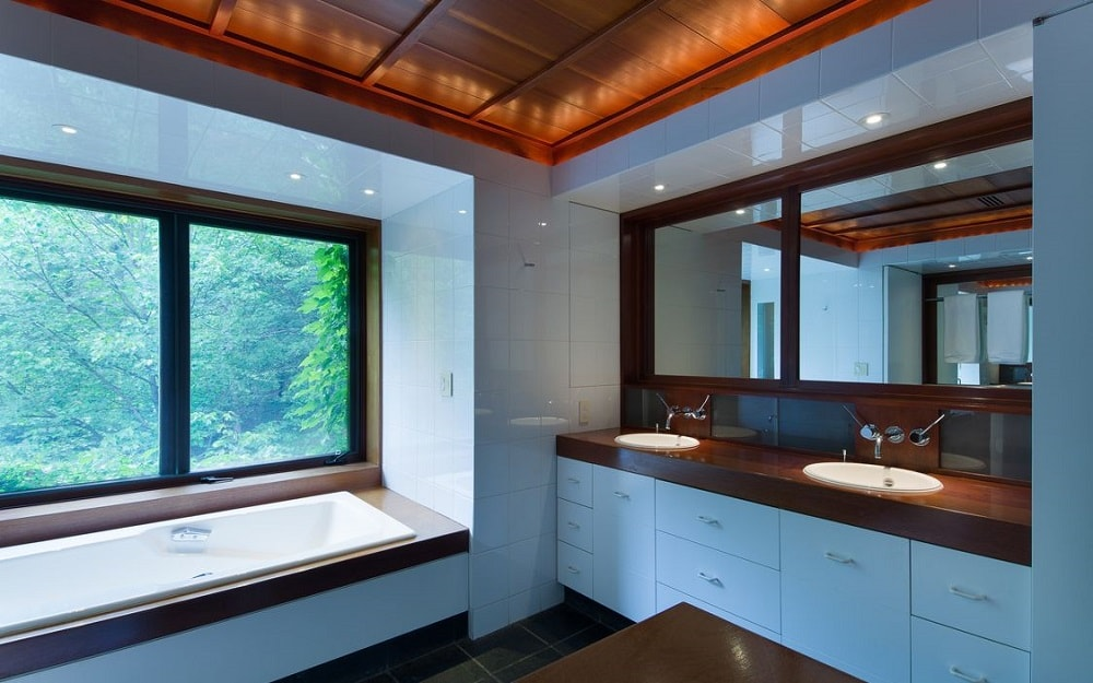 This is the bathroom with a two-sink vanity built into the wall with white drawers and dark brown accent to match the bathtub underneath the large glass window. Image courtesy of Toptenrealestatedeals.com.