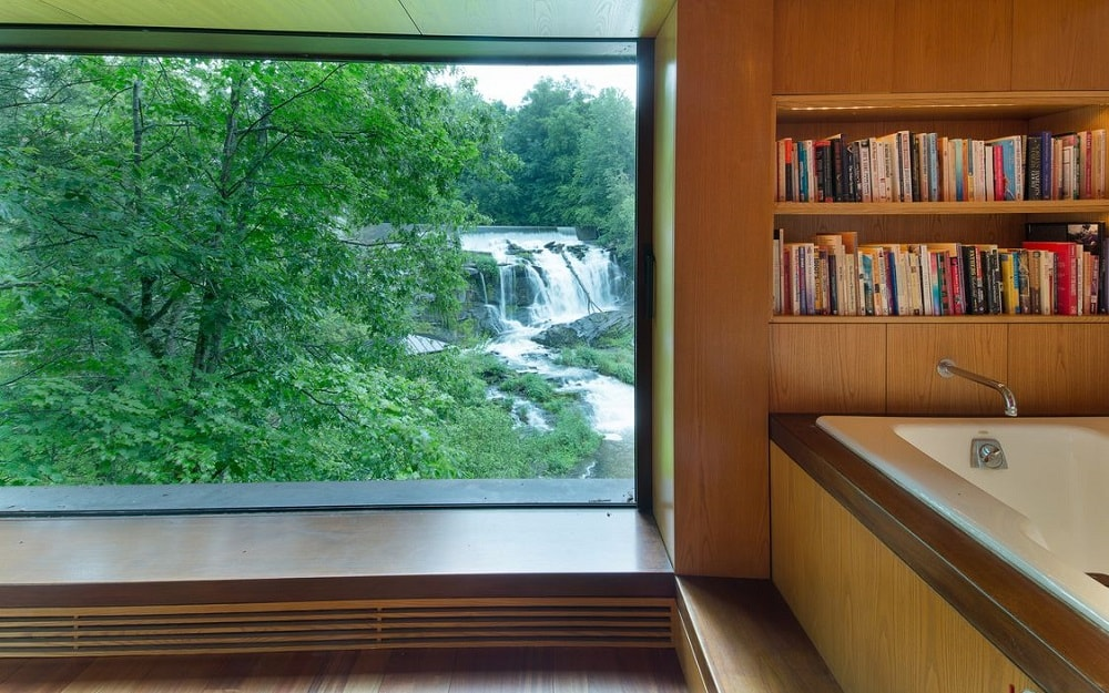 This end of the bathtub shows that it has a built-in bookshelf filled with books. Next to it is a large glass wall. Image courtesy of Toptenrealestatedeals.com.