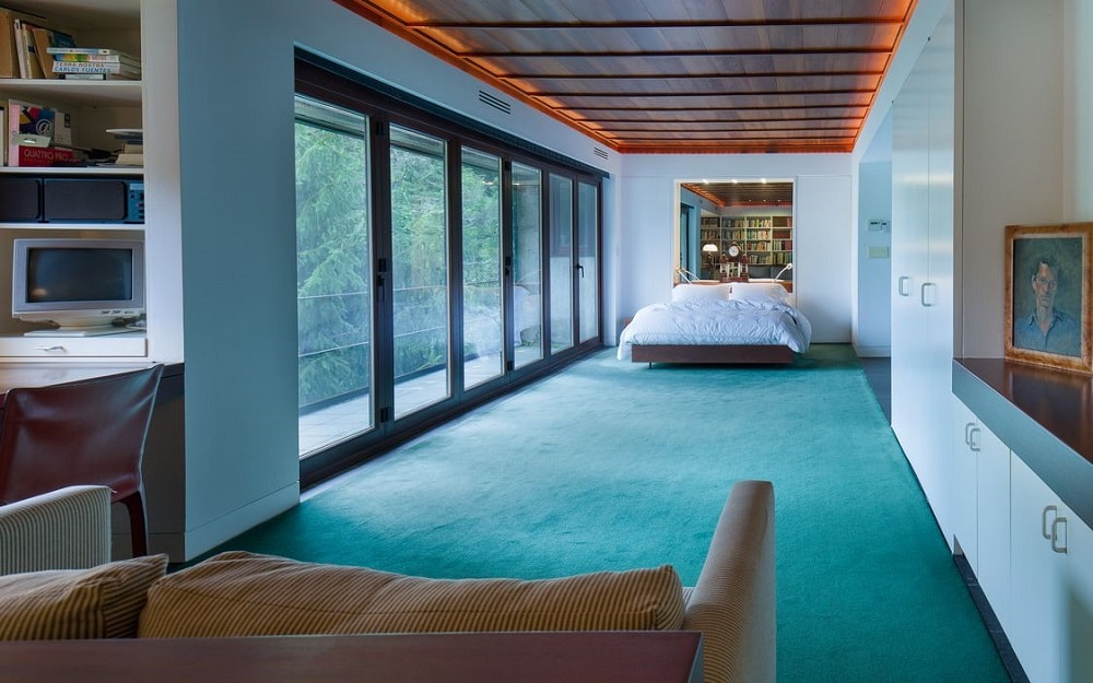 This is the bedroom with a wide glass wall on the side that brings in natural lighting for the green carpeted flooring that makes the platform bed on the far side stand out. Image courtesy of Toptenrealestatedeals.com.