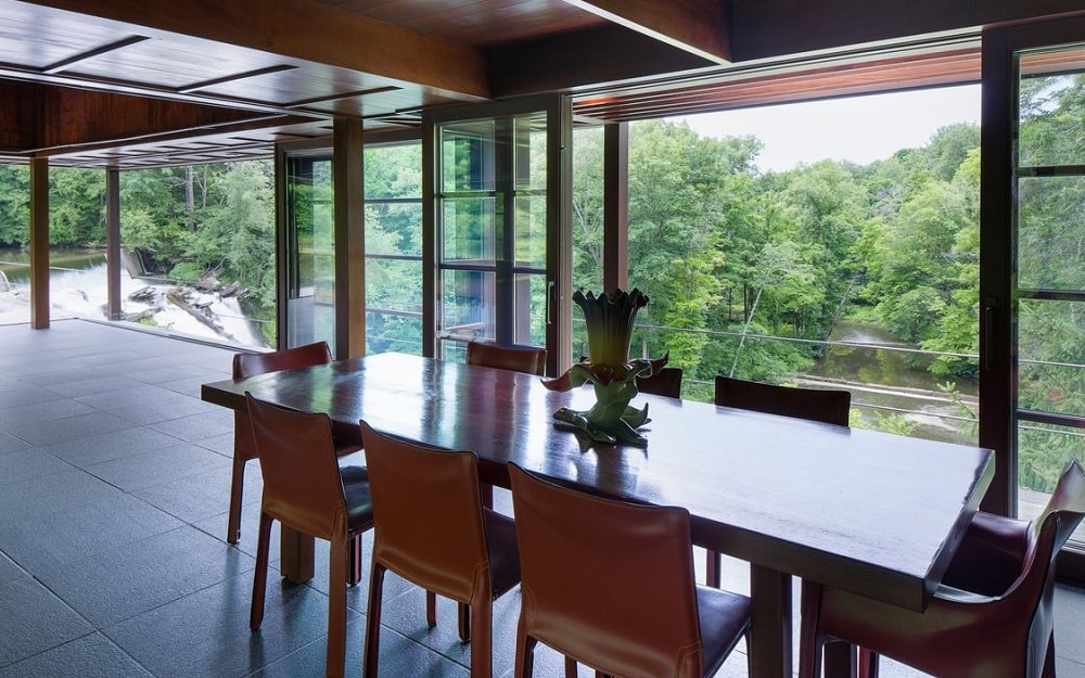This is a closer look at the wooden dining table. It matches the wooden tone of the ceiling and the chairs surrounding it. The highlight of the dining area is the landscape view through the glass walls. Image courtesy of Toptenrealestatedeals.com.