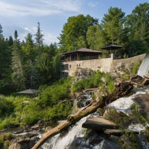 This is a look at the house from the vantage of the waterfalls. Here you can see that the house built right on edge of the waterfall. It also has a background of tall trees that give the exterior glass walls color. Image courtesy of Toptenrealestatedeals.com.