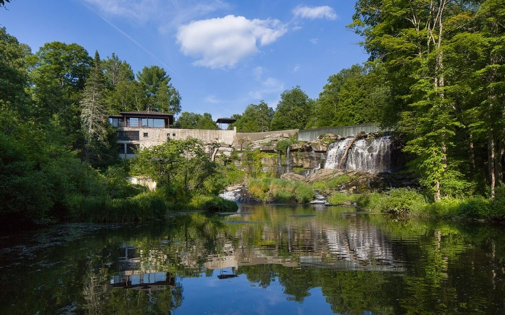 This is a view of the house from the river. Here you can appreciate the 60-foot elevation and the beauty of the waterfalls beside it. Image courtesy of Toptenrealestatedeals.com.
