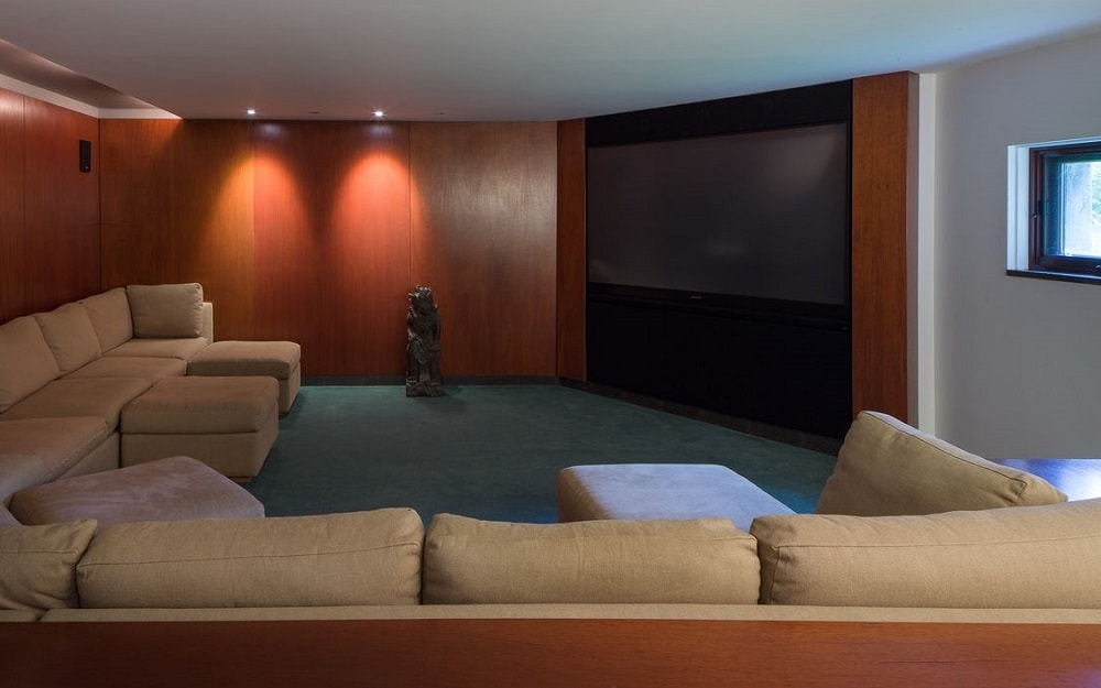 This is the home theater with lots of comfortable sitting that has brown cushions facing a large screen on the other side. Image courtesy of Toptenrealestatedeals.com.