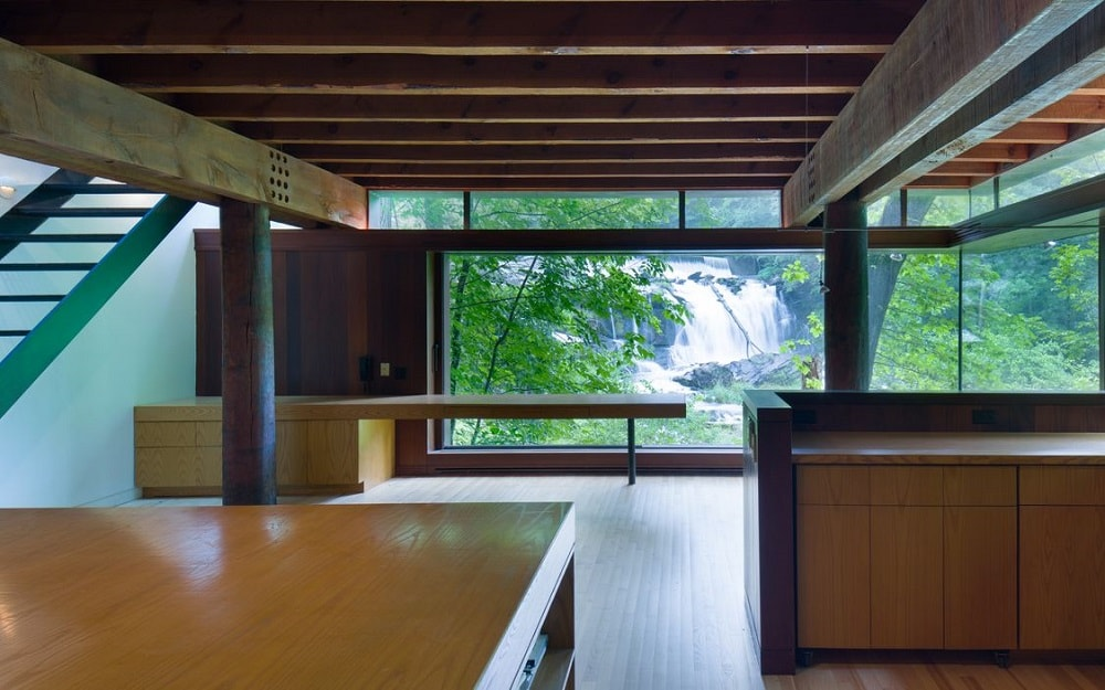 Here is the bare and minimalist kitchen with built-in wooden structures and islands that match the wooden ceiling with exposed beams illuminated by the large glass walls. Image courtesy of Toptenrealestatedeals.com.