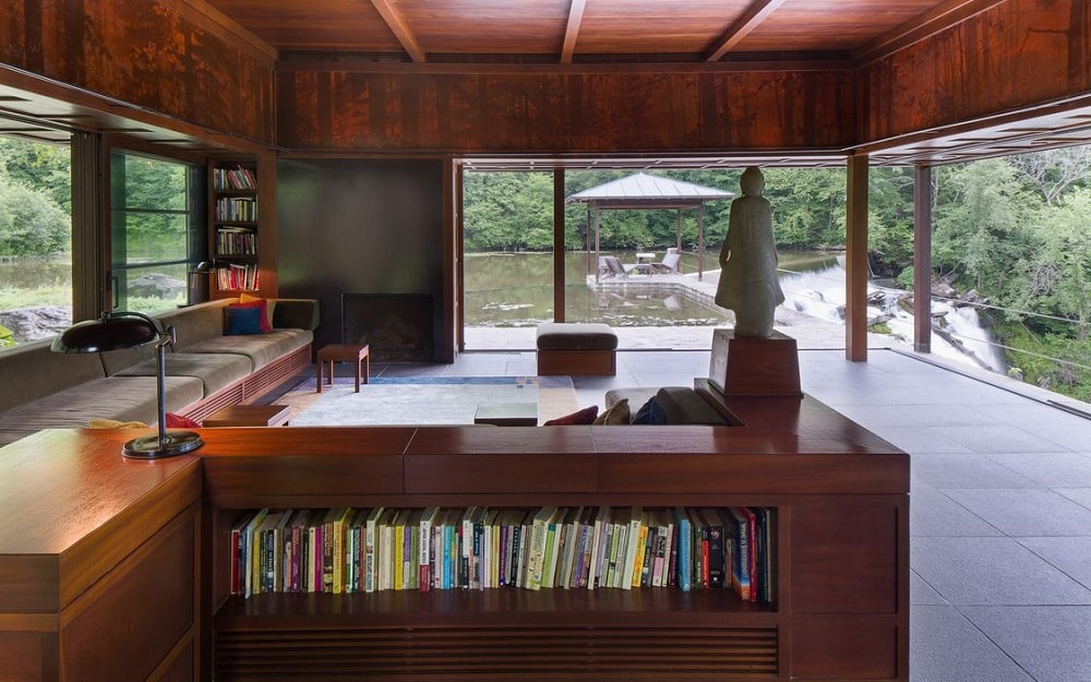 This side of the living room shows a built-in bookshelf behind the wooden built-in bench with a dark brown tone to match the ceiling. Image courtesy of Toptenrealestatedeals.com.