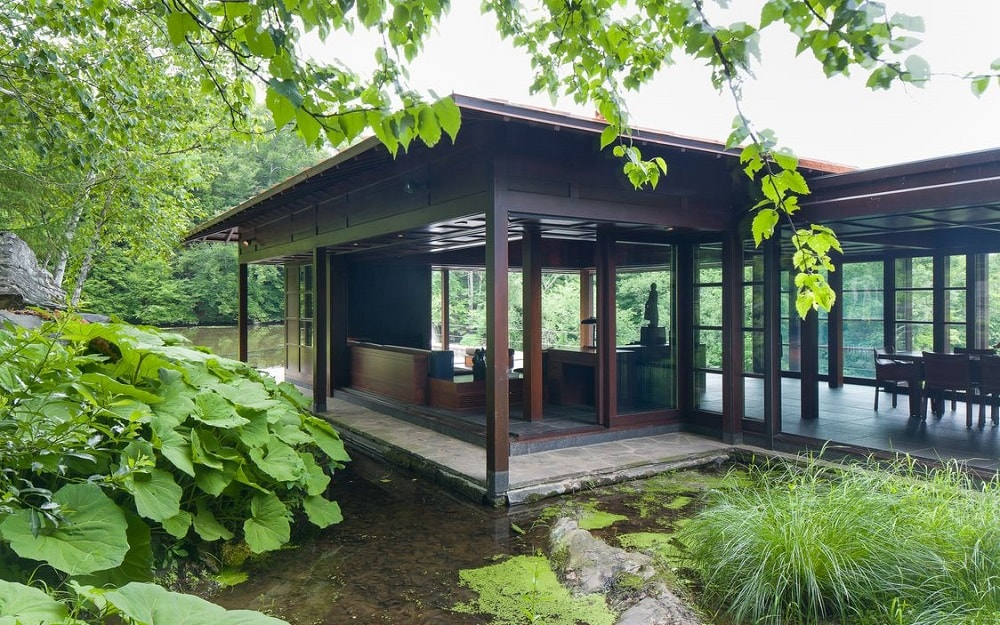 This side of the house focuses on the covered patio just outside the living room. It has a concrete floor that is bordered on three sides with running water giving it an island-like look. Image courtesy of Toptenrealestatedeals.com.