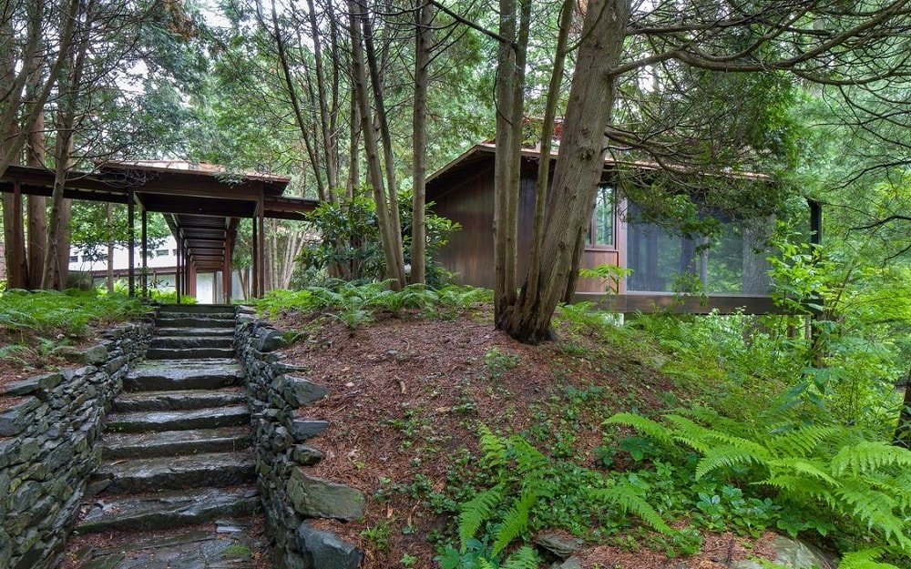 This side of the house showcases rustic and textured stone walkways and steps leading up to the house and down to the side of the waterfall. Here you can see the tall trees that give shade to the glass exteriors. Image courtesy of Toptenrealestatedeals.com.