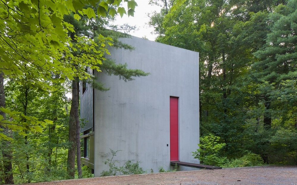 This side of the has a simple concrete wall with a red accent containing a side-door connected to a narrow bridge. Image courtesy of Toptenrealestatedeals.com.