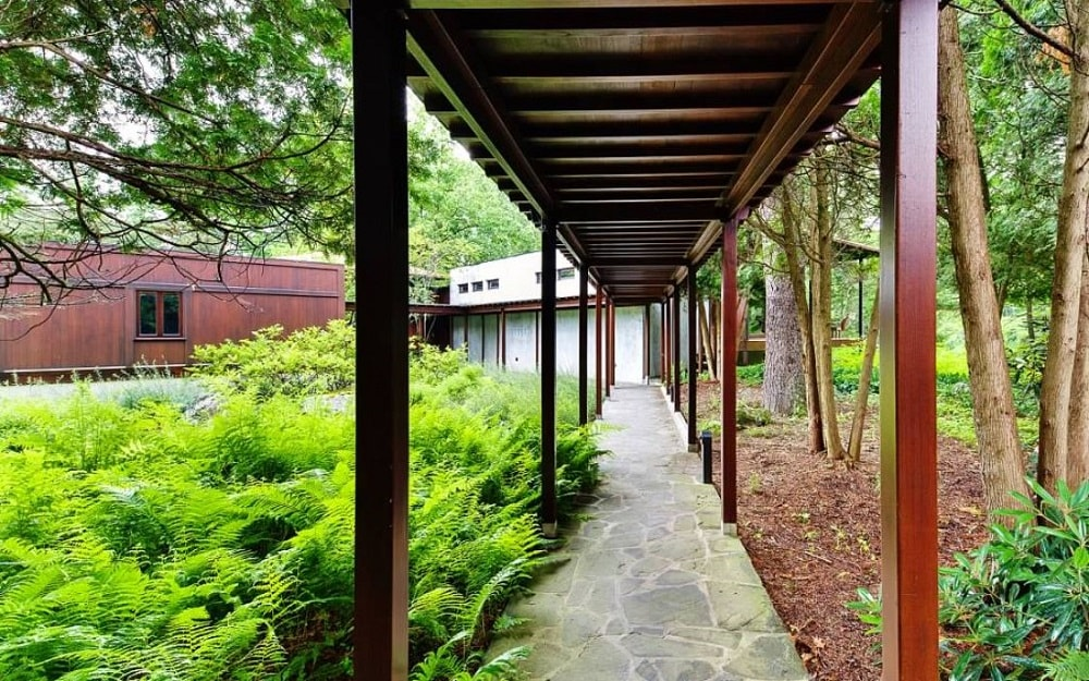 This is the covered walkway connecting the various sections of the house adorned with thick shrubs on the side. Image courtesy of Toptenrealestatedeals.com.